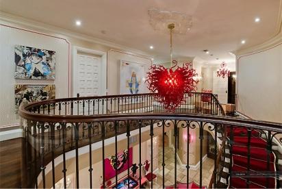 Subindo as escadas do saguão, um lustre ousado contrasta com a construção clássica da mansão