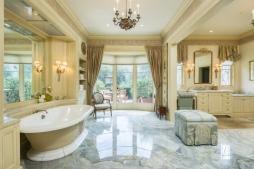 Detalhado em mármore, o banheiro da suíte também aposta em cores claras